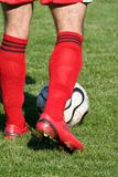 Feet of the football player and a ball. Royalty Free Stock Images