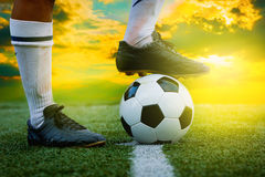 Feet of football player tread on soccer ball Royalty Free Stock Photo