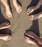 Feet of four Persons at the beach. Feet at the wet beach in harmonic pattern stock photo