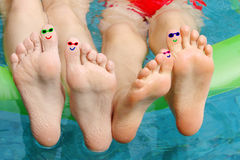 Feet fun faces. In a swimming pool Royalty Free Stock Photography