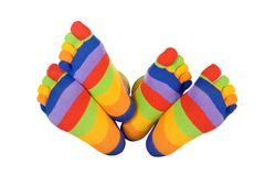 Feet in funny socks. Man and woman feet in funny socks touching (isolated) - concept for compatible soulmates, togetherness and fun stock photography