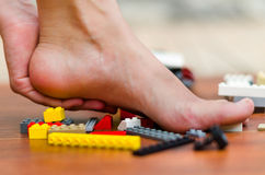 A feet get hurt with some legos on the floor. Various colors, red, white, yellow, gray, black.  stock photo