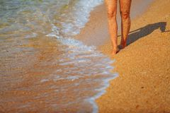 Feet girl on the beach. Waves running to the shore royalty free stock image