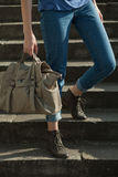 Feet girl holding a bag on the stairs in jeans Stock Photos