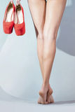 Feet girl holding red shoes Royalty Free Stock Images