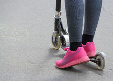 Feet of girl in jeans riding a scooter. Feet of girl in jeans and pink sneakers riding a scooter. Outdoor sports, urban stock photos