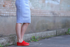 Feet girl in red slip-on on background of concrete wall. Stock Image