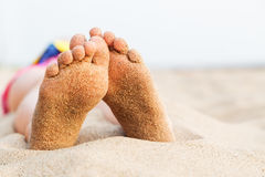 Feet girl relaxing on the beach after swimming. In the sea background Royalty Free Stock Images