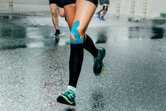 Feet girl runners in compression socks. And taping on his knees, running on wet asphalt stock photography