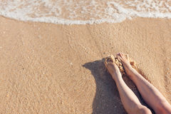 Feet girl in the sand on the beach near water Royalty Free Stock Photos