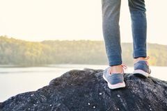 Feet girl standing on the rock in nature winter season. Relax time on holiday concept travel,selective and soft focus,tone of hipster style Royalty Free Stock Photography