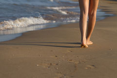 Feet of girl waking on sand. Feet of unrecognizable young woman walking on the sand Royalty Free Stock Photos