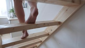 Legs go down the stairs. Feet of a girl walking down a wooden staircase stock footage