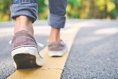 Feet of girl walking in the road. And forest background, Relax time on holiday concept travel ,color of vintage tone and soft focus stock photography