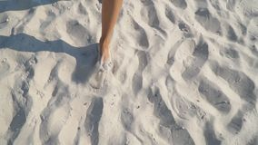 Feet of a girl walking on the sand. Close-up feet of a girl walking on the sand stock video