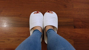 Feet of Girl Wear White Slippers and Blue Jeans on the Wooden Floor Background Stock Photography