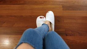Feet of Girl Wear White Slippers and Blue Jeans on the Wooden Floor Background Stock Photo