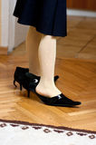 Girl in womens shoes. The feet of a girl wearing an adult women's shoes stock photo
