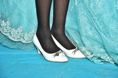 Feet girl in white shoes and black stockings near the turquoise bridesmaid dresses Stock Image