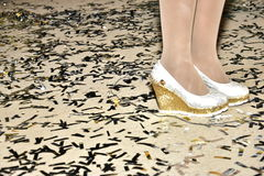 Feet girl in white shoes and stockings and confetti on the floor Stock Photos