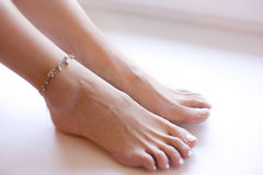Feet of girl, woman with pedicure and bracelet Stock Image