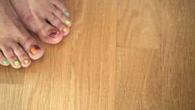 Feet girl on the wooden floor with a nice pedicure stock footage