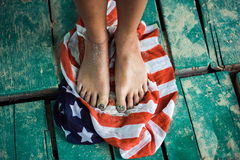 Feet girls stand on the flag of the United States. green board Royalty Free Stock Photos