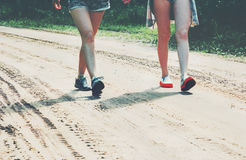 Feet girls walking on the road Lifestyle Travel. And friendship concept summer vacations Stock Images