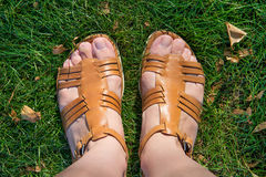 Feet on the grass. The photo shows the legs in sandals on a green grass. View from above Royalty Free Stock Photo