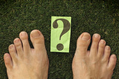 Feet on green grass which has a question mark on it Royalty Free Stock Image