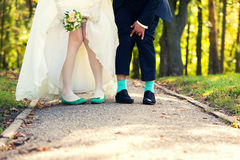 Feet of  groom and the bride with green socks. Ridiculous feet of the groom and bride. Green socks and shoes Royalty Free Stock Photo