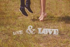 Feet of groom and bride and white love letters Royalty Free Stock Photography