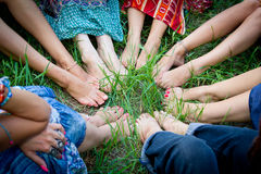 Feet of group of young girls in a circle. Bare feet of group of young girls in a circle on a green grass royalty free stock photos