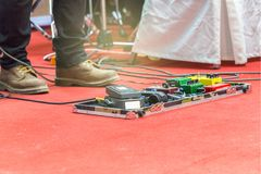 Feet of guitar player on a stage with set of distortion effect pedals. Selective focus Royalty Free Stock Image