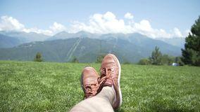 Feet of a guy while relaxing on lawn against firs, blue sky, clouds and mountains. Hiking in mountains. Sneakers shoes stock video