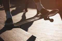 Feet of guy on skateboard. Skater does grind trick. Hobby of active youth. Work on every move Stock Image