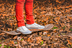Feet in gym shoes of a young man on a skateboard in the fall Stock Photos