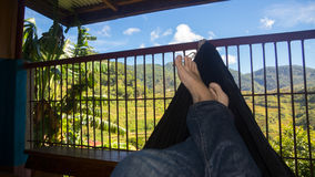 Feet and Hammock with Maligcong Rice Terraces in Background. Tourst relaxing in a hammock with vast rice terraces in the backdrop Royalty Free Stock Image