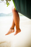 Feet in Hammock. Woman relaxing in hammock at the white sand beach of Koh Surin Island, Thailand royalty free stock photos