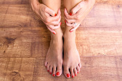 Feet and Hands. Feet placed on a wooden background with hands holding ankles Stock Image