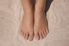 Feet and hands on the beach Royalty Free Stock Image