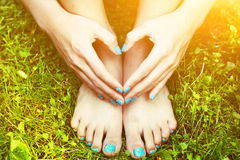 Feet and hands with creative teens manicure and pedicure on the green grass lawn background Stock Photo