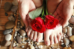 Feet Hands Roses. Pair of pretty red roses with hands and feet on river rocks and bamboo mat royalty free stock image