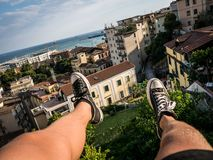Feet hanging above city rooftop from helicopter. Image showing Feet with Shoes dangling from a Helicopter with the Italy Skyline and Coast in the Background. The royalty free stock photography
