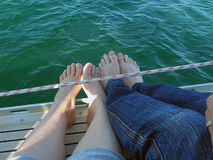 Feet hanging off a boat royalty free stock photography