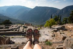 Feet hanging over ancient site of Delphi, Greece. Tourist`s feet hanging over ancient site of Delphi, Greece stock images