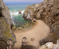 Feet hanging over beach cliff Stock Photos