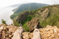 Feet hanging over the cliff rock top view. Baikal.  Royalty Free Stock Images