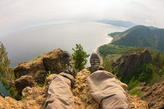 Feet hanging over the cliff rock top view. Baikal.  Royalty Free Stock Photos