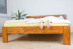 Feet hanging over end of bed. Human feet dangling over end of bed; face and body of person not visible stock photos